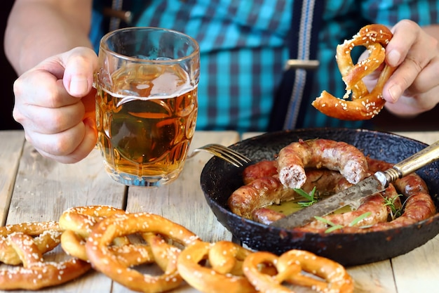 Mężczyzna przy stole ze szklanką piwa, precelem i patelnią z kiełbaskami. święto oktoberfest.