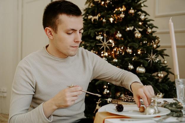 Mężczyzna przy świątecznym stole. choinka na złotym jasnym wnętrzu