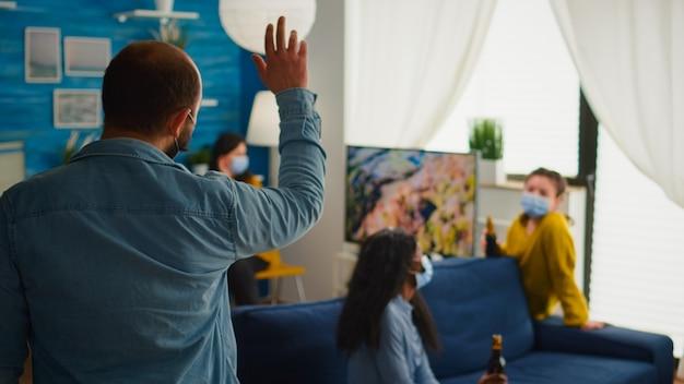Mężczyzna przychodzący na imprezę z przyjaciółmi noszący maskę zapobiegającą rozprzestrzenianiu się koronawirusa, kobiety trzymające butelki piwa towarzysko w salonie mieszkania. ludzie cieszący się czasem podczas epidemii covid 19
