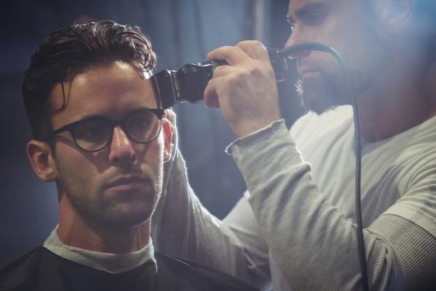 Mężczyzna przycina włosy trymerem