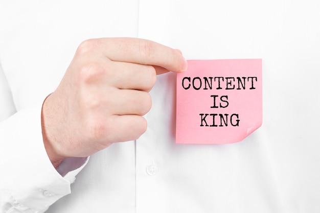 Mężczyzna przyczepia czerwoną naklejkę z napisem content is king do swojej białej koszuli