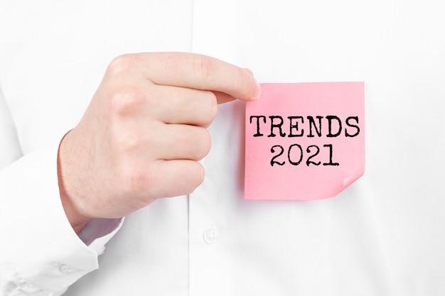 Mężczyzna przyczepia czerwoną naklejkę z napisem trendy 2021 do swojej białej koszuli