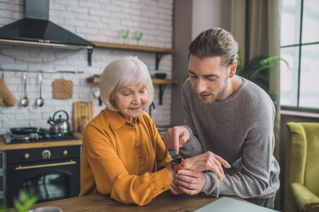 Mężczyzna przyczepia zegarek do ręki swojej mamy