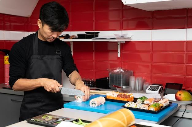 Mężczyzna przygotowujący zamówienie sushi na wynos