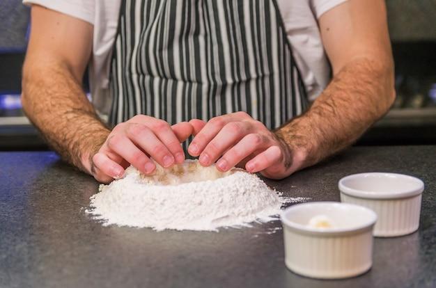 Mężczyzna przygotowuje ciasto do pizzy na stole z czarnego granitu