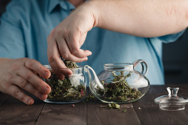 Mężczyzna przygotowuje herbaty ziołowe w czajniku
