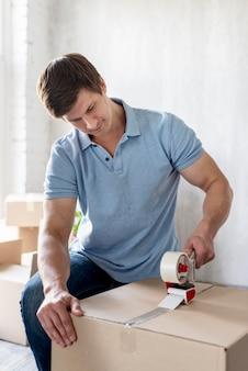 Mężczyzna przygotowuje pudełko z taśmą klejącą do wyprowadzki