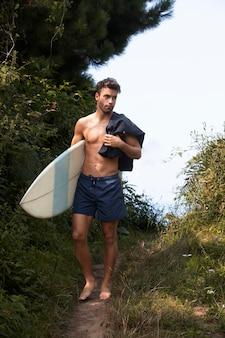 Mężczyzna przygotowuje się do korzystania ze swojej deski surfingowej