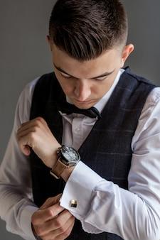 Mężczyzna przygotowuje się do pracy zapinając biznesową koszulę. poranne przygotowanie pana młodego przed ślubem