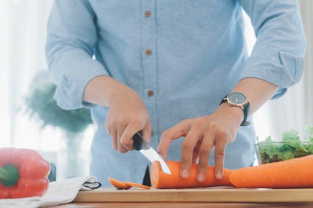 Mężczyzna przygotowuje smaczne i zdrowe jedzenie w domowej kuchni