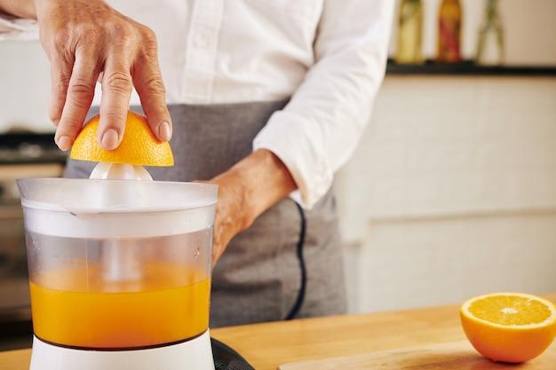 Mężczyzna przygotowuje sok pomarańczowy