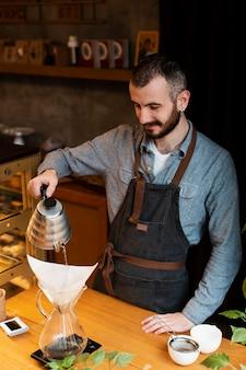 Mężczyzna przygotowywa kawę dla sklep z kawą