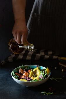 Mężczyzna przygotowywa sałatki z grilla łososia z awokado