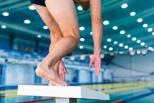 Mężczyzna przygotowywa skakać w pływackim basenie