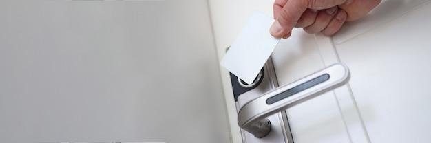 Mężczyzna przykładający plastikową kartę do zamka drzwi, aby otworzyć zbliżenie