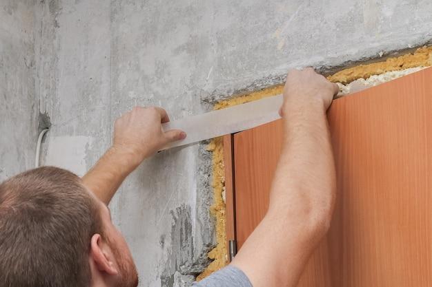 Mężczyzna przykleja białą papierową taśmę. zbliżenie. remont w domu.