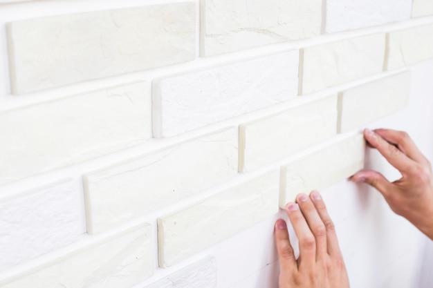 Mężczyzna przykleja tynk z białych płytek na ścianie. naprawa mieszkania w domu