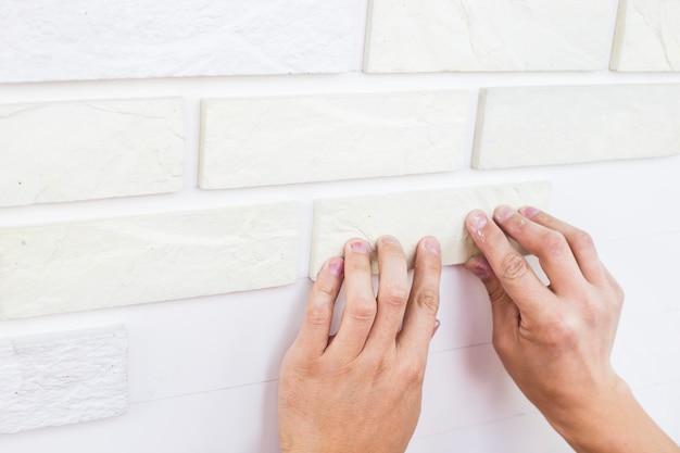 Mężczyzna przykleja tynk z białych płytek na ścianie