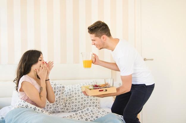 Mężczyzna przynosi śniadanie w łóżku dla kobiety