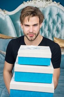 Mężczyzna przystojny kochanek i prezent. niespodzianka dla ukochanej. prezenty dla ukochanej. romantyczna niespodzianka. urodzinowy poranek. obchody walentynek. seksowna niespodzianka dla kobiet. człowiek w luksusowej sypialni z pudełkiem.