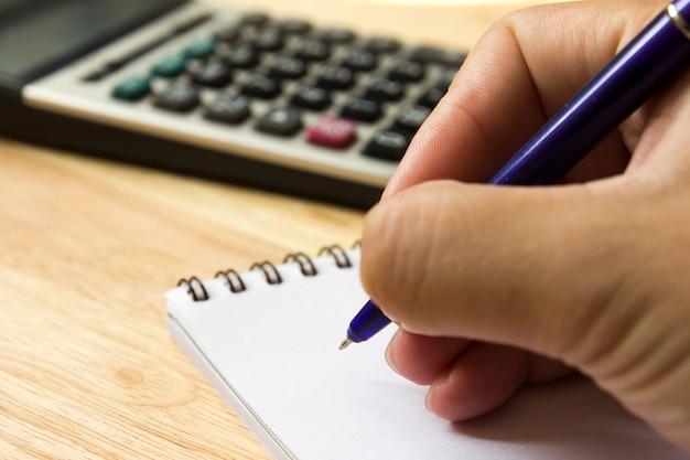 Mężczyzna przytrzymaj pióro na notatki na książki z kalkulatorem