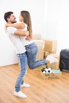 Mężczyzna przytula kobietę na tle kartonowych pudeł