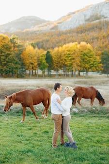 Mężczyzna przytula kobietę na tle pasących się koni w lesie jesienią