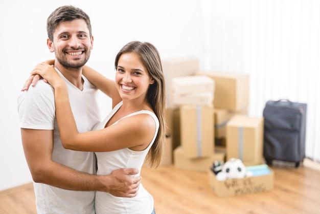 Mężczyzna przytula kobietę na tle pudeł