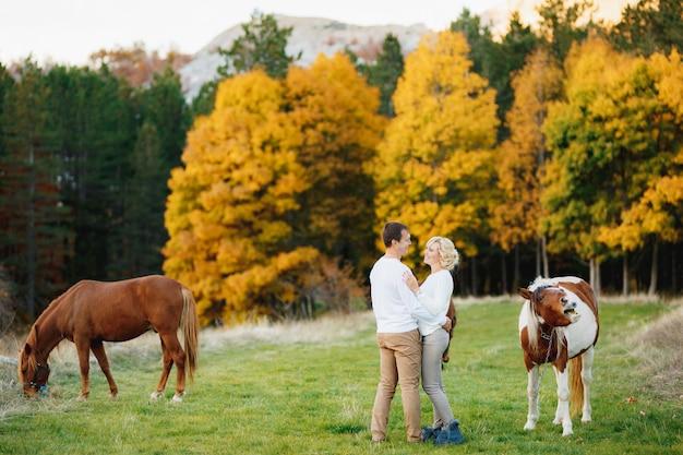 Mężczyzna przytula kobietę stojąc na trawniku w jesiennym lesie konie pasące się na trawniku