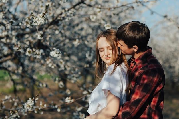 Mężczyzna przytula swoją czułą dziewczynę od tyłu, stojąc w kwitnącym ogrodzie w słoneczny wiosenny dzień.