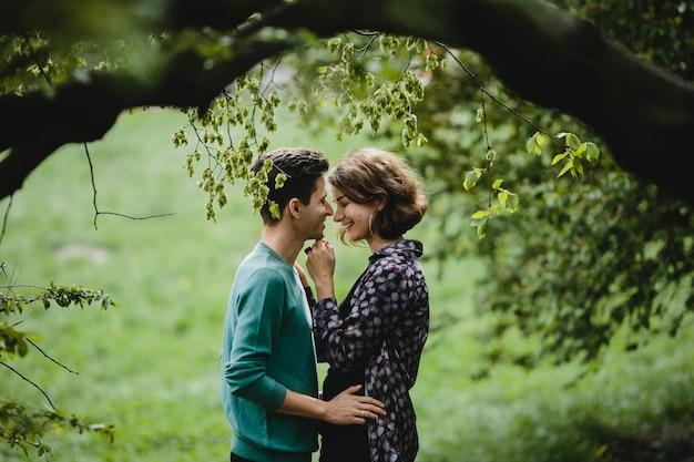 Mężczyzna przytula swoją żonę i uśmiechają się do siebie