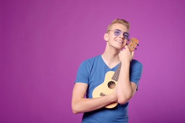 Mężczyzna przytula ukulele na gitarze na fioletowo