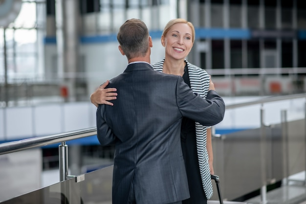 Mężczyzna przytulający kobietę z walizką na lotnisku