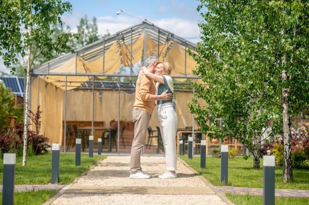 Mężczyzna przytulający swoją uśmiechniętą małżonkę na zewnątrz
