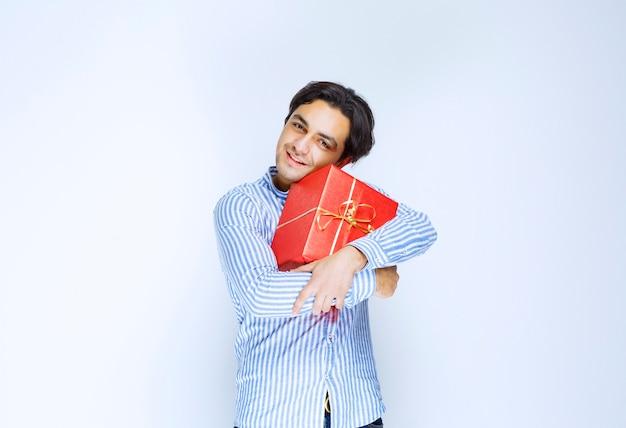 Mężczyzna przytulający swoje cenne czerwone pudełko. zdjęcie wysokiej jakości