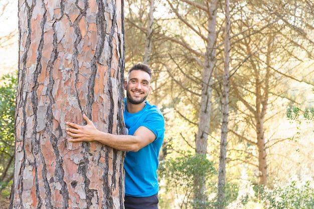 Mężczyzna przytulenia drzewo w uroczym lesie