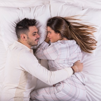 Mężczyzna przytulenia kobieta w łóżku