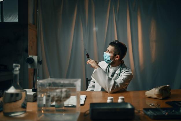 Mężczyzna psychiatra w masce trzymając strzykawkę z uspokajającym, szpitalem psychiatrycznym. lekarz w poradni dla chorych psychicznie