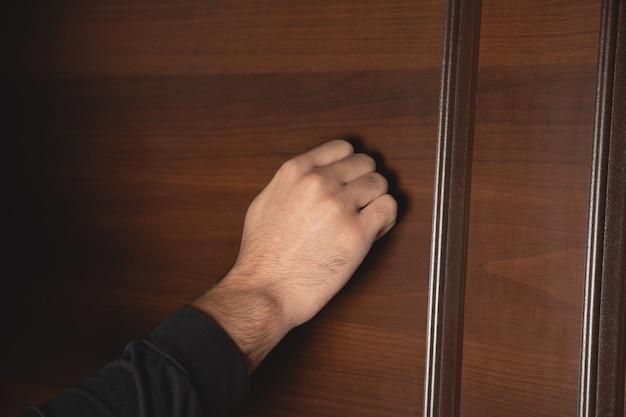 Mężczyzna puka do drzwi