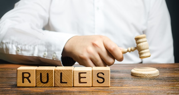 Mężczyzna puka młotek publikuje nowe zasady i prawa. ustalanie jasnych zasad i ograniczeń.
