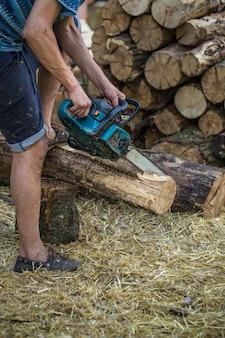 Mężczyzna rąbanie drewna piłą łańcuchową