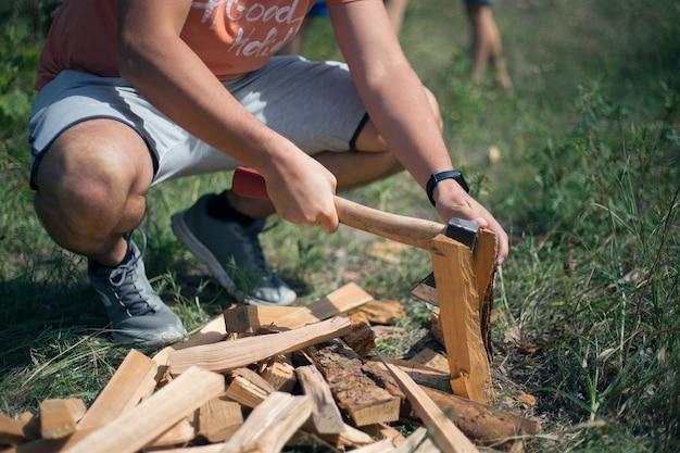 Mężczyzna rąbanie drewna siekierą na ulicy