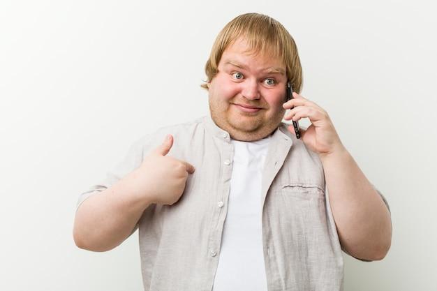 Mężczyzna rasy kaukaskiej plus size dzwoniący przez telefon zaskoczony wskazuje na siebie, uśmiecha się szeroko