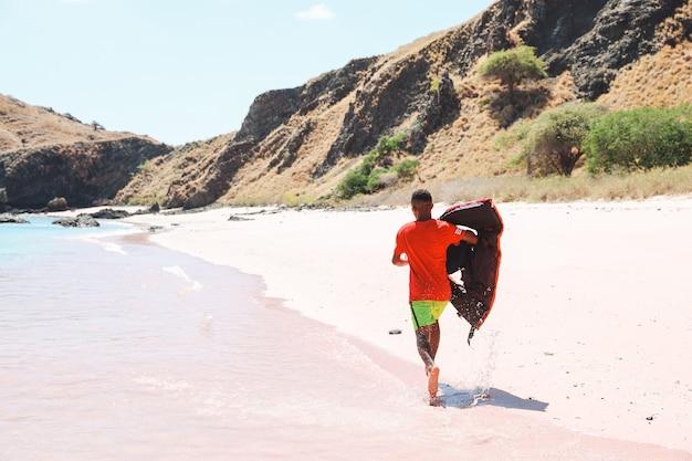 Mężczyzna ratownik biegający po różowej plaży z kamizelką ratunkową