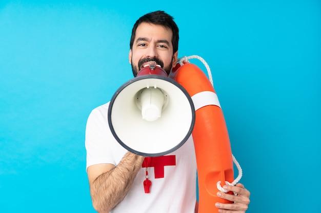 Mężczyzna ratownik na pojedyncze niebieskie ściany krzyczy przez megafon