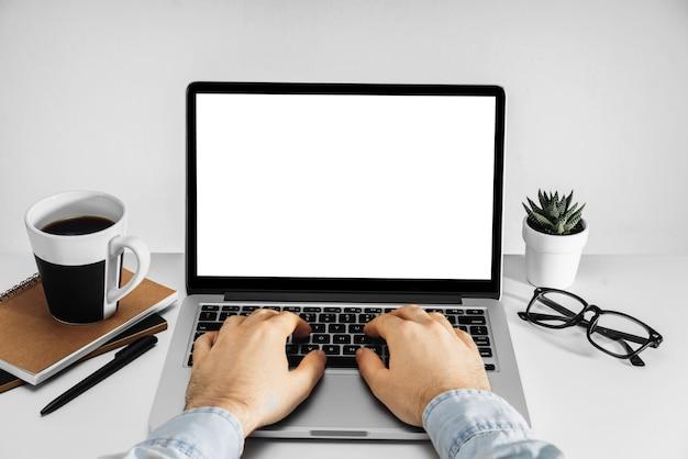Mężczyzna ręce do pracy na komputerze przenośnym z pustym białym ekranem