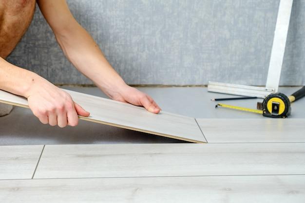 Mężczyzna ręce kładzie drewniany panel podłogi laminowanej w pomieszczeniu z bliska. podłogi laminowane, miejsce na kopię