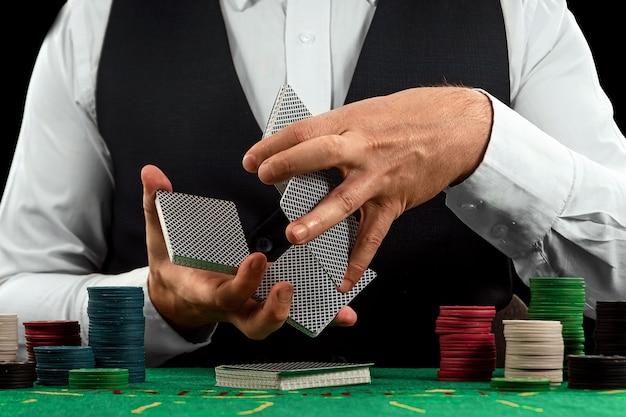 Mężczyzna ręce krupier tasuje karty zbliżenie
