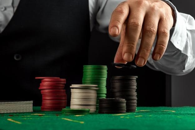 Mężczyzna ręce krupier w kasynie i gry w żetony na zbliżenie zielony szmatką