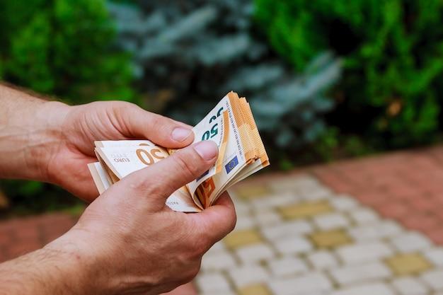 Mężczyzna ręce licząc nam banknoty euro. liczenie lub wydawanie pieniędzy.